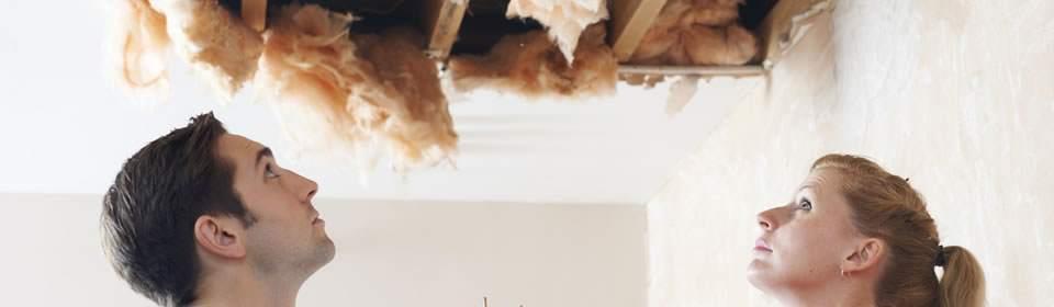 man en vrouw kijken naar lekkage in plafond